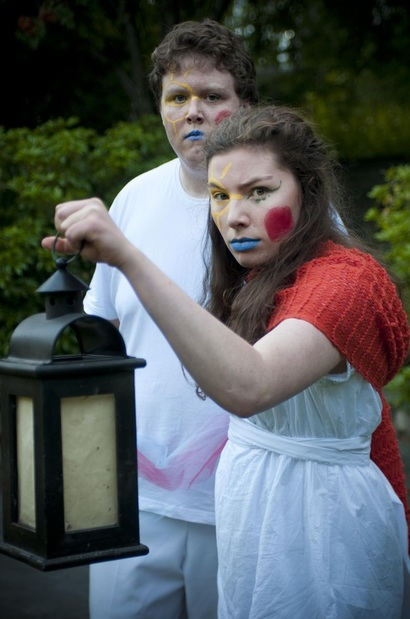 Julie is holding a lantern in front of her. She wears a white dress with  a red scarf draped around her shoulders. She has bright yellow, blue and red face paint. Behind her, Francis stands dressed in white with the same colourful face paint.