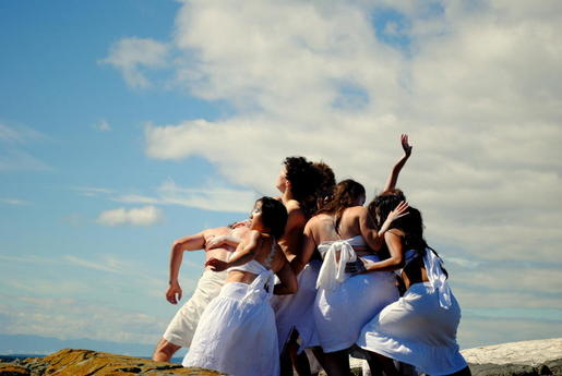 A cluster of performers dressed in white cloth are pressing against one another. They are on a rock in the ocean and there is a cloudy sky behind them.